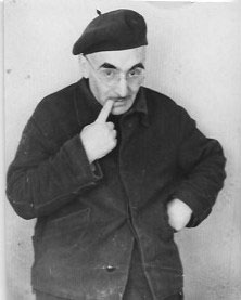 """A scientist sucks ideas out of his own finger"", a comic photograph of Mikhail Verzhbinsky in a beret with a finger in his mouth"