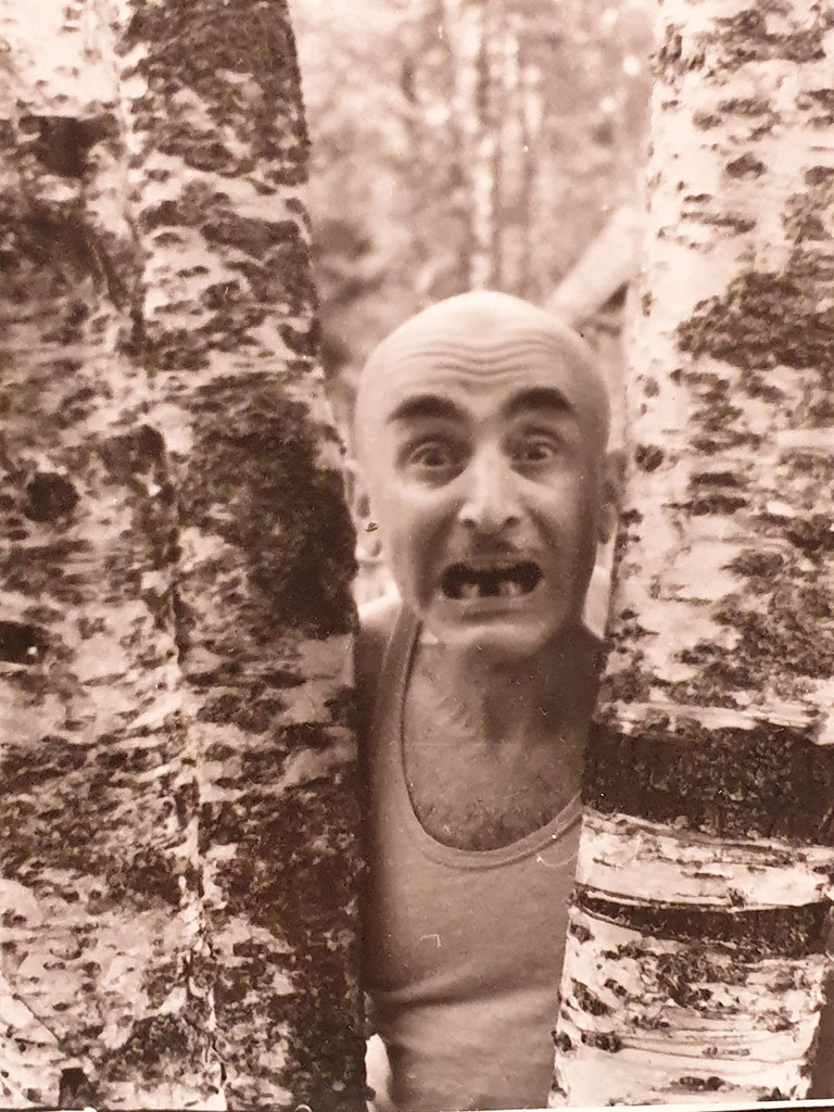 """Candidate of Mathematical Sciences, Associate Professor of the Mining Institute Verzhbinsky M. L."", a comic photograph of Mikhail Verzhbinsky between two birches with blackened teeth, 1960"