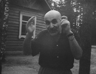 """That's so small,"" a comic photograph of Mikhail Verzhbinsky showing something small with his hands"