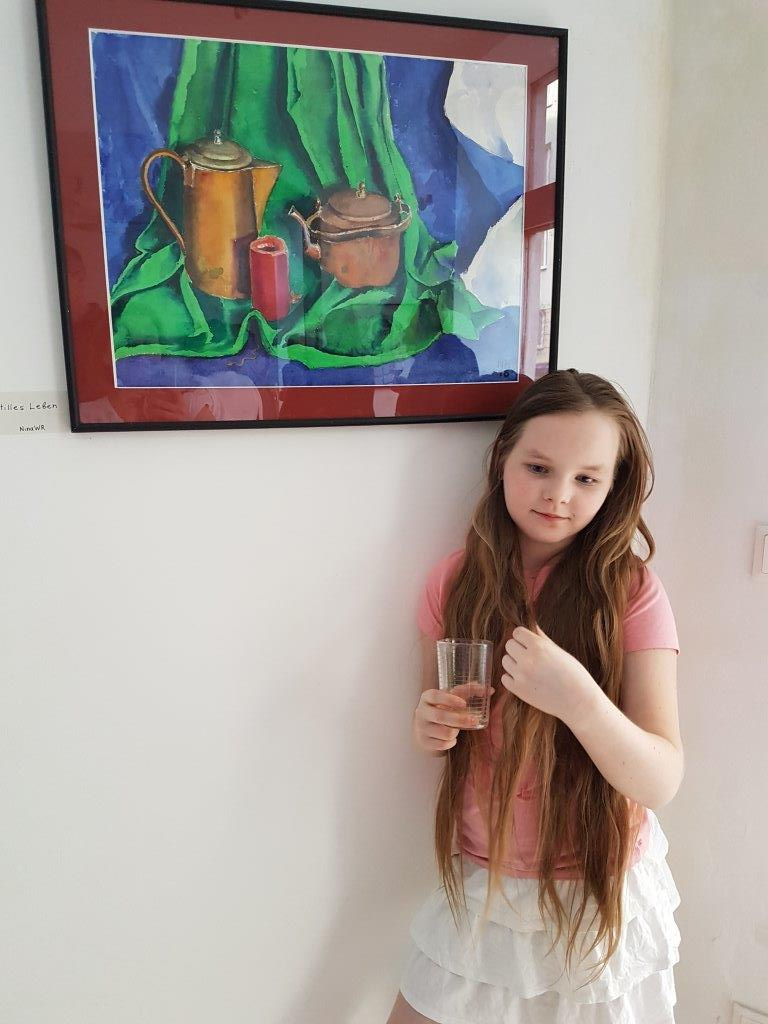 The student in front of the painting by the teacher